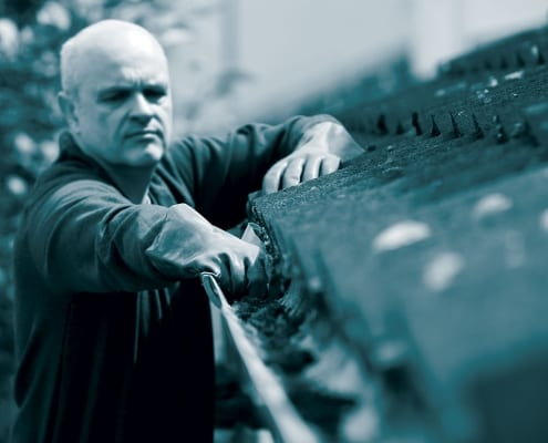property maintenance, man clearing gutter